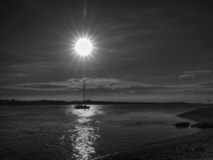 Levée de soleil en Angleterre et voilier quittant la rade